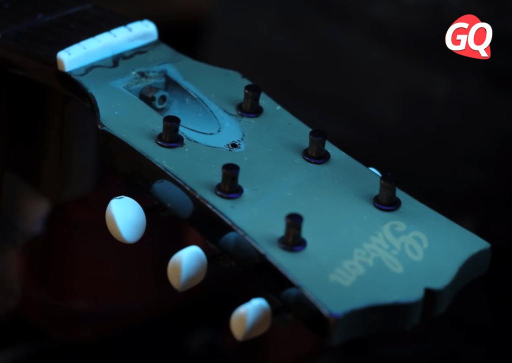 Cabeçote de um violão Gibson J-45 1946 iluminado com luz negra ou ultravioleta.